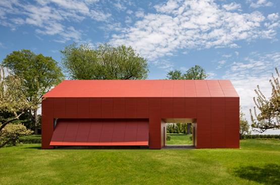 据报道,纽约的罗杰-费里斯建筑事务所(Roger Ferris + Partners)最近在康涅狄格州建造了一个类似谷仓的艺术家工作室兼住宅。这幢房子的外部采用大红条形装饰。 这幢建筑的几何形状,使人联想新英格兰的农村建筑,但整个建筑采用了与众不同的大红水平板条装饰外表面。 罗杰-费里斯建筑事务所说:这幢建筑与传统的房子形成鲜明的对比,它的极简主义的功能设计和效率,是对普通的新英格兰建筑形式的重新解释。 建筑表面的板条,用一种叫做瑞士珍珠(Swisspearl)的高端纤维水泥材料做成。这种板条用于建